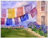 Watercolor painting of colorful hangings with the ocean as backdrop